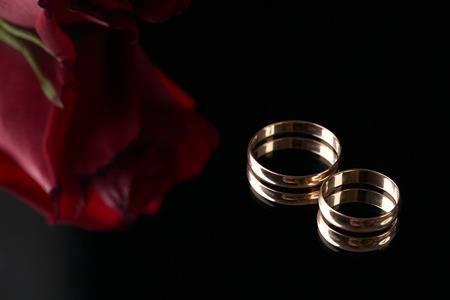75790613-close-up-van-twee-gouden-trouwringen-en-huwelijksboeket-van-rode-rozen-op-zwarte-achtergrond-gouden-